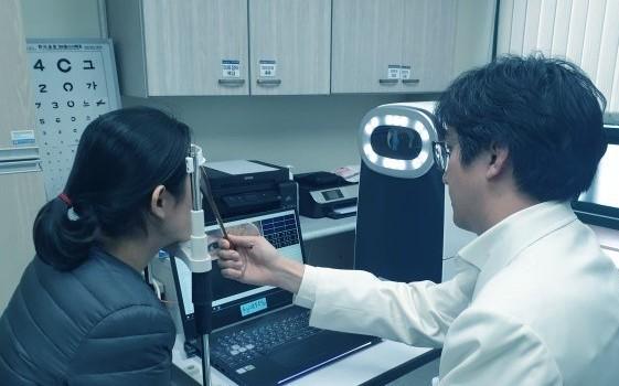 기자가 직접 사시각 측정 의료로봇을 체험해보고 있다.