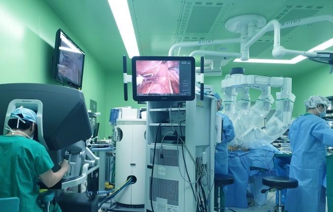 다빈치 로봇은 환자의 복부에 구멍을 내고 로봇팔이 각각 기구를 넣어 수술한다. 사진 맨 왼쪽이 집도의인 민병소 연세대 세브란스병원 로봇수술센터장. 콘솔박스에서 3차원 영상을 보면서 원격으로 조종한다.