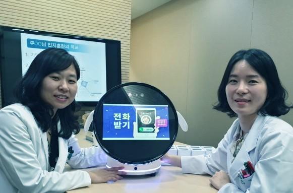 김건하 이대목동병원 신경과 교수(왼쪽)가 로보케어와 공동 개발한 인지 훈련 로봇 ′보미′을 선보이고 있다. 나연아 신경심리사 지도하에 환자와 1대1로 인지훈련을 할 수 있다.