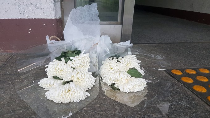 방화 살인 참사가 난 경남 진주시 한 아파트 출입구에 19일 주민 누군가가 하얀 국화를 놓았다. 연합뉴스 제공