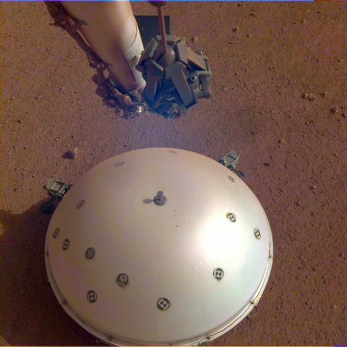 미국항공우주국(NASA)의 화성탐사선 인사이트가 화성 표면에 지진계를 내려놓고 있다. 사진제공 NASA