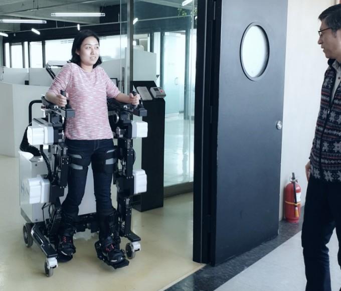 기자가 이진원 연구소장의 도움을 받아 엑소워크를 타고 복도를 이동해보고 있다. 스스로 움직이는 것처럼 자유롭게 걸어다닐 수 있다. 최고속도는 시속 2km로 느리지만 안전하다.