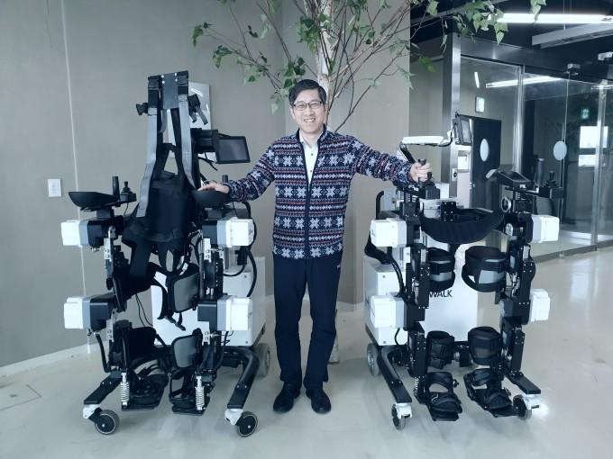 이진원 에이치엠에이치 연구소장이 자유롭게 이동가능한 편마비 환자용 하지재활로봇′엑소워크 프로(오른쪽)′와 척수마비환자용으로 개발한 하지재활로봇(왼쪽)과 함께 서 있다.