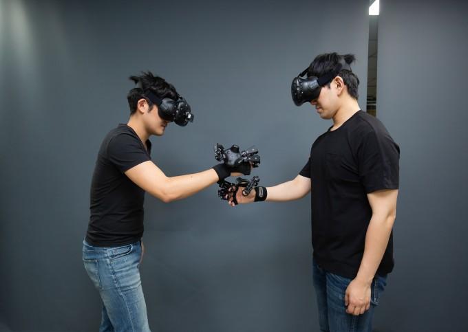 인체감응실감교류솔루션연구단 연구원들이 자체개발한 공간 터치감 지원 핸드 모션캡쳐 외골격 장치와 HMD를 착용한 채 시연을 하고 있다. 만들어 낸 가상공간에 현실 속 움직임이 절묘하게 결합하고, 여러 명이 같은 가상공간에서 협업도 할 수 있다는 게 특징이다. 사진 남윤중