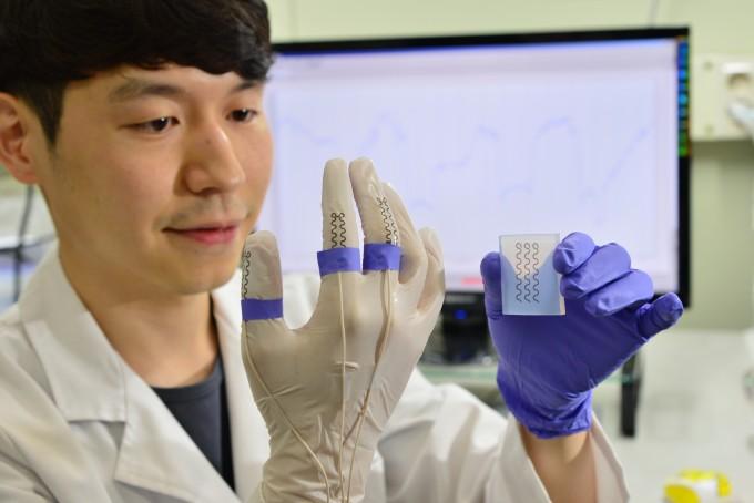 KIST 스핀융합연구단 연구원이 개발한 전사 프린팅 기술로 실험용 장갑 위에 고성능 센서를 구현하여 손가락 움직임을 감지하는 실험을 하고 있다. 사진제공 KIST