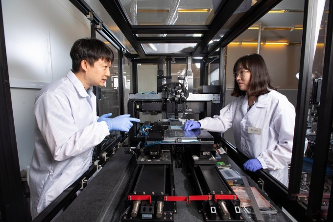 연구단의 정현준 박사(왼쪽)과 원세정 박사가 마이크로LED를 효율적으로 옮길 수 있는 메타물질 응용 장비를 살펴보고 있다. 메타물질은 특이한 물성을 구현해 기존 기술이나 재료로는 할 수 없던 일들을 수행할 수 있게 해준다. 사진 제공 홍덕선 작가