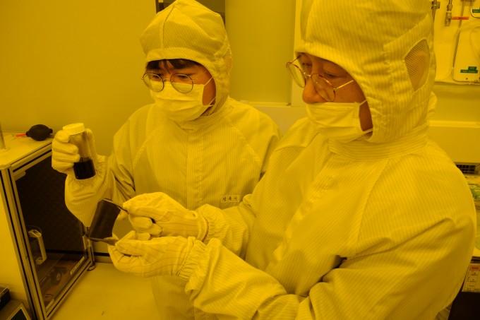 민복기 ETRI 연구원과 최춘기 책임연구원이 전도성 나노 소재 용액과 전자파 차폐 소재의 탄성을 시험하고 있다. ETRI 제공