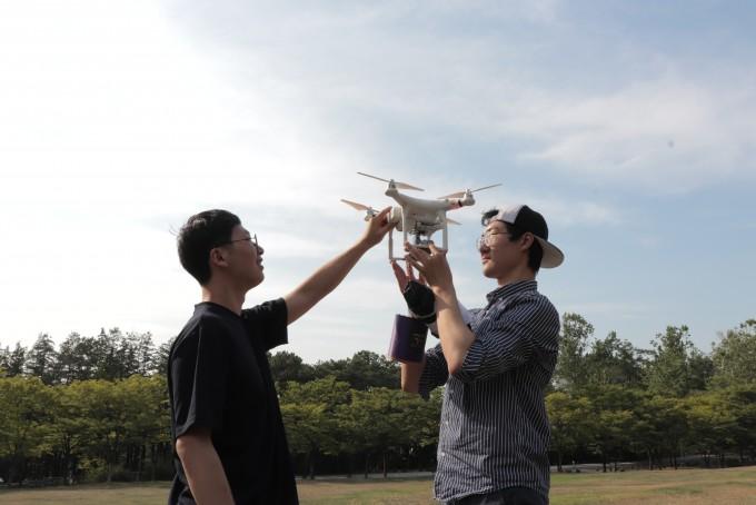 김동석 공동대표(왼쪽)와 서바다 공동대표가 드론을 통해 콩돌 스페이스 로보틱스가 제작한 캔위성을 시험하고 있다. 이수현씨 제공