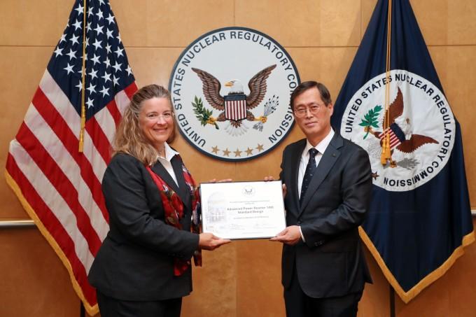 26일(현지시간) 워싱턴D.C. 미국 원자력규제위원회(NRC) 본부에서 열린 인증서 수여식 행사에서 정재훈 한수원 사장(오른쪽)이 NRC 위원(Annie Caputo)으로부터 인증서를 받고 있다. 한국수력원자력 제공.