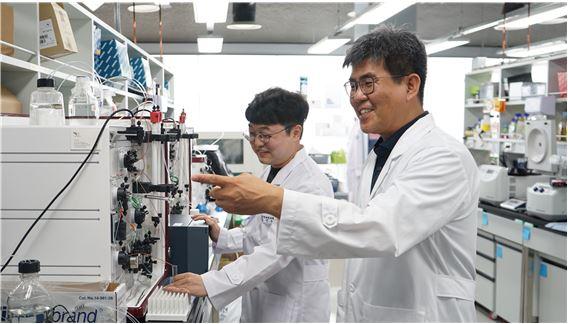 임현호 한국뇌연구원 책임연구원과 박건웅 연구원이 FPLC를 이용해 세포막단백질 CLC-ec1이 정제되는 모습을 관찰하고 있다. 한국뇌연구원 제공