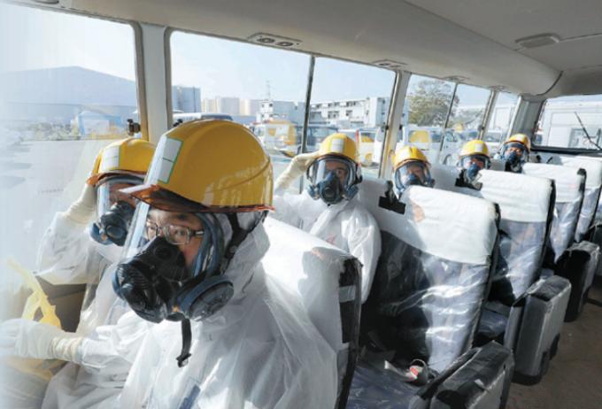 후쿠시마 제1원전에서 방진복과 방독마스크 등 보호장비를 착용한 한국, 독일, 베트남 등 기자들이 오염수를 정화하는 다핵종제거설비(ALPS) 가동실로 가는 버스에 탑승해 있다. 원전 내부의 97% 지역은 방독면 없이 다닐 수 있지만, 오염수 관련 시설을 출입할 때는 반드시 보호장비를 착용해야 한다. 폴라리스이미지 제공