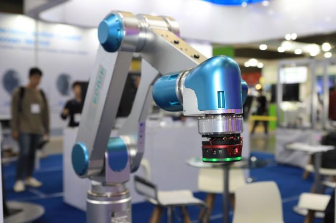 도현민 한국기계연구원 첨단생산장비연구본부 책임연구원 연구팀은 산업용 로봇팔에 부착해 사람이 원하는 방향으로 로봇을 조작하는 장치를 개발했다. 사진은 이달 9일 열린 ′2019 로보월드′에 전시된 장치의 모습이다. 로봇 팔 끝에 달려있는 장치가 제어장치다. 한국기계연구원 제공