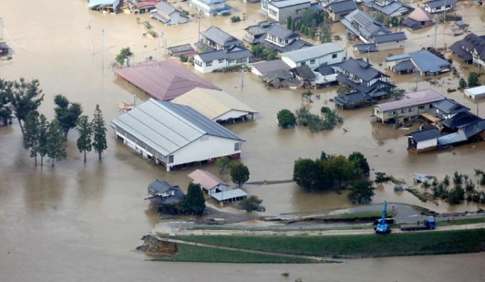 태풍 ′하기비스′가 몰고 온 폭우 속에 13일 일본 나가노현 나가노시에서 지쿠마강(江)의 무너진 둑 주변 가옥들이 침수된 모습.  AFP/연합뉴스 제공