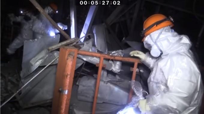 일본 원자력규제위원회 직원들이 이달 12일 후쿠시마 제1 원전 3호기 건물 내부에서 흰 방호복과 방독면을 착용한채 폭발 사고 현장을 살펴보고 있다. 일본 원자력규제위원회 유튜브 캡처