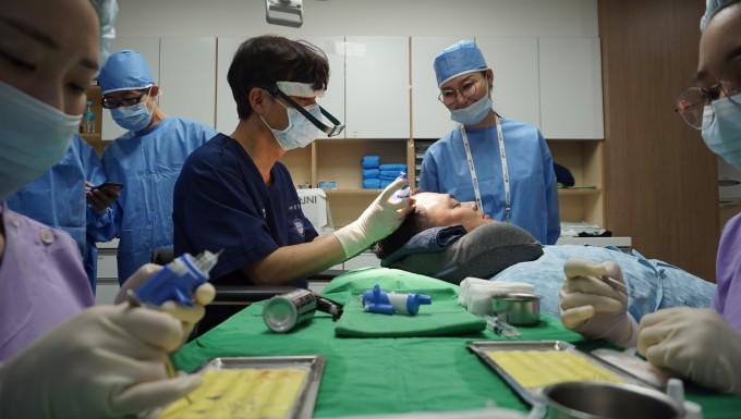 ETRI 연구팀이 개발한 '연발형 모발이식기'로 경북대 김문규 교수팀이 실제 모발 이식 수술을 하고 있다. ETRI 제공
