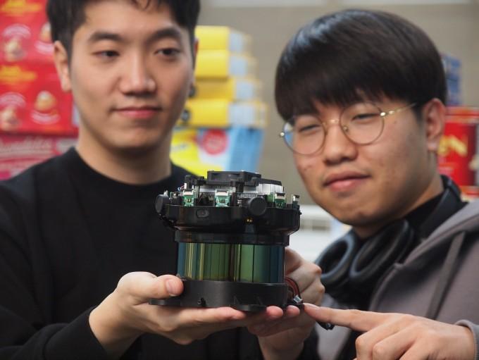 곽인범 폴라리스3D 대표(왼쪽)와 이호용 개발이사가 개발 중인 초소형 실내 자율주행로봇용 기기를 들어 보이고 있다. 뒤에 자율주행 로봇이 활약할 마트 환경을 재현한 매대가 보인다. 포항=윤신영 동아사이언스 기자