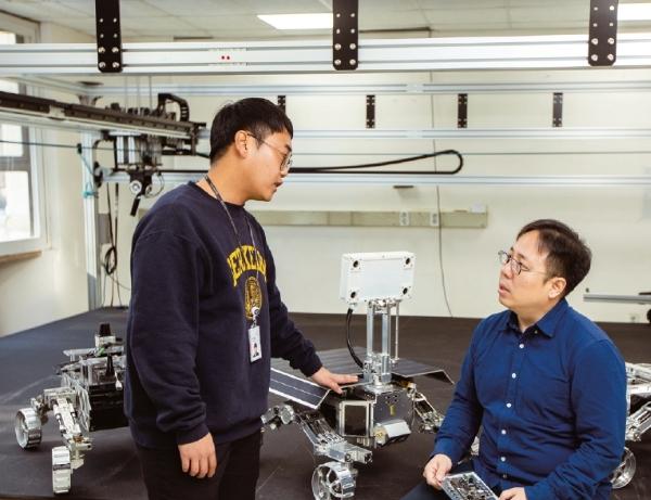 2019년 12월 6일 한국형 달탐사 로버의 첫 시연을 앞두고 상의 중인 한국과학기술연구원(KIST) 의 이우섭 책임연구원(오른쪽) 과 문대호 연구원. 천장에 달린 레일에서 내린 줄 반대쪽에 추를 달아 로버 무게를 6분의 1로 줄였다. 달에서 지구보다 작은 중력을 받는 효과를 내기 위해서다. 현진 제공