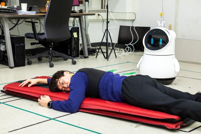 혼자 사는 노약자나 환자가 자가격리돼 간병인을 만나기 어렵다면 위험이 크다. 쓰러질 경우 병원에 알리기도 힘들다. 이럴 때 인공지능(AI)과 로봇을 결합한 헬스케어로봇이 큰 도움이 된다. 김문상 광주과학기술원(GIST) 교수가 개발한 노약자 헬스케어 AI로봇이 24일 오후, 쓰러진 연기를 한 연구원을 발견하고 낙상 경고를 병원에 보내고 있다. 동아사이언스 제공