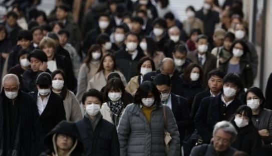 신종 코로나바이러스(코로나 19)의 충격이 확대되고 있는 가운데 18일 일본 도쿄의 직장인들이 대거 마스크를 착용하고 걸어가고 있다. 도쿄AP/연합뉴스 제공