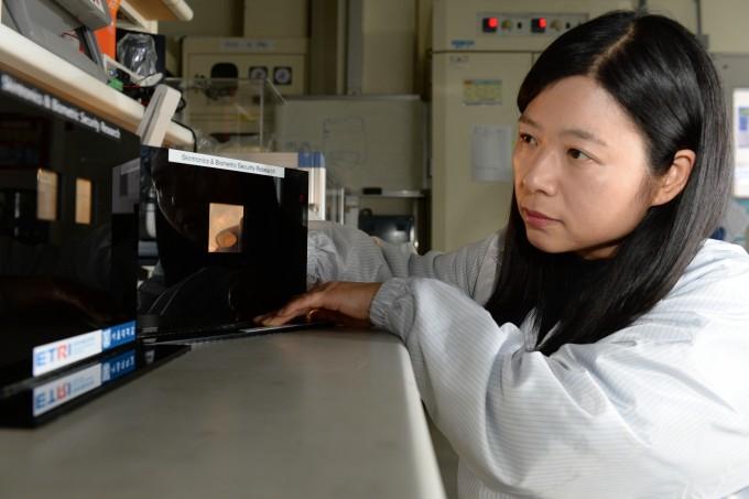 오지영 한국전자통신연구원(ETRI) 책임연구원이 초고감도 압력센서의 발광 성능을 시험하고 있다. ETRI 제공