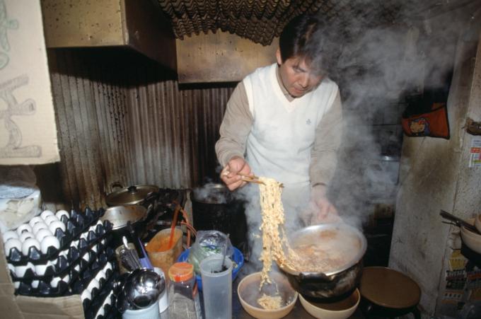 고열을 이용해 순간적으로 끓인 양은 냄비의 라면을 옮겨 담고 있는 모습이다. 연합뉴스 제공