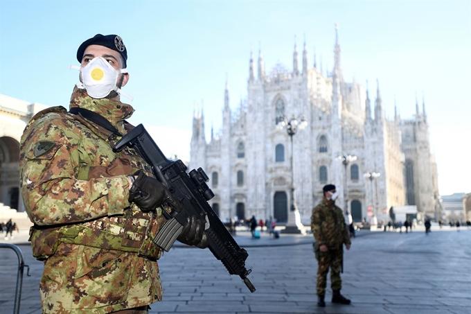 마스크를 쓴 이탈리아 군인들이 24일 신종 코로나바이러스 감염증(코로나19) 확산의 여파로 폐쇄된 밀라노 두오모 대성당 앞에서 경비를 서고 있다. 밀라노 로이터/연합뉴스 제공