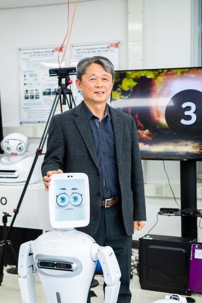 김문상 GIST 헬스케어로봇센터장이 연구실에서 개발한 자폐스펙트럼증후군 어린이를 위한 놀이 치료 로봇과 함께 자세를 취했다. 인공지능(AI)기술과 로보틱스가 결합한 로봇은 최근 다양한 질병을 보다 환자 친화적으로 치료할 대안으로 주목 받고 있다. 동아사이언스 제공
