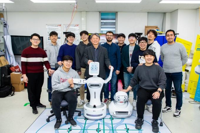 GIST 헬스케어로봇센터 연구실에서 김문상 센터장(가운데)과 연구원들이 자폐스펙트럼증후군 어린이를 위한 놀이 치료 로봇과 함께 자세를 취했다. 인공지능(AI)기술과 로보틱스가 결합한 로봇은 최근 다양한 질병을 보다 환자 친화적으로 치료할 대안으로 주목 받고 있다. 동아사이언스 제공