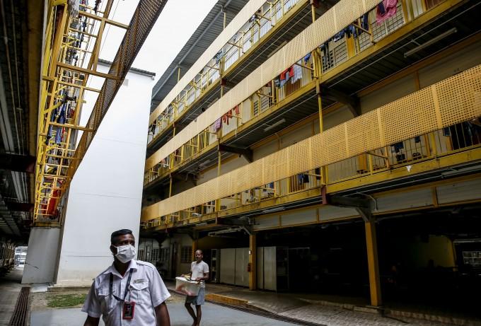 싱가포르 정부 관계자들이 집단 감염이 발생한 외국인 노동자 기숙사를 마스크를 쓰고 지나가고 있다. EPA/연합뉴스 제공