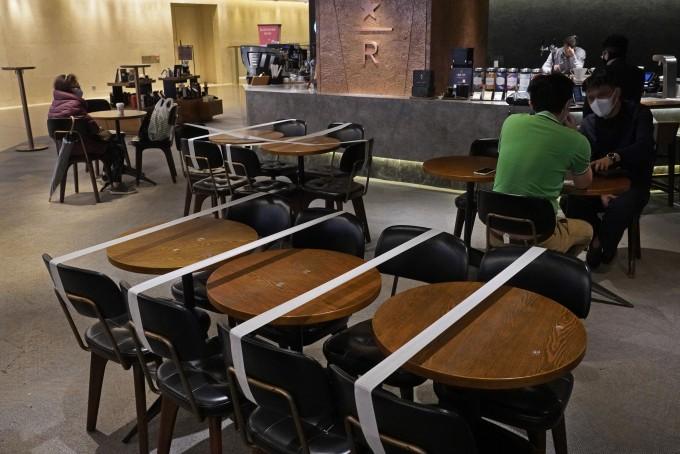 지난달 30일 홍콩에 있는 한 스타벅스 매장의 테이블과 의자에 신종 코로나바이러스 감염증(코로나19) 차단을 위한 사회적 거리두기 일환으로 테이프가 붙여져 있다. 홍콩 정부는 코로나19 대책으로 음식점의 경우 테이블당 인원을 4명으로 제한하고, 테이블 간 거리도 1.5m씩 띄우도록 했다. 홍콩 AP=연합뉴스 제공