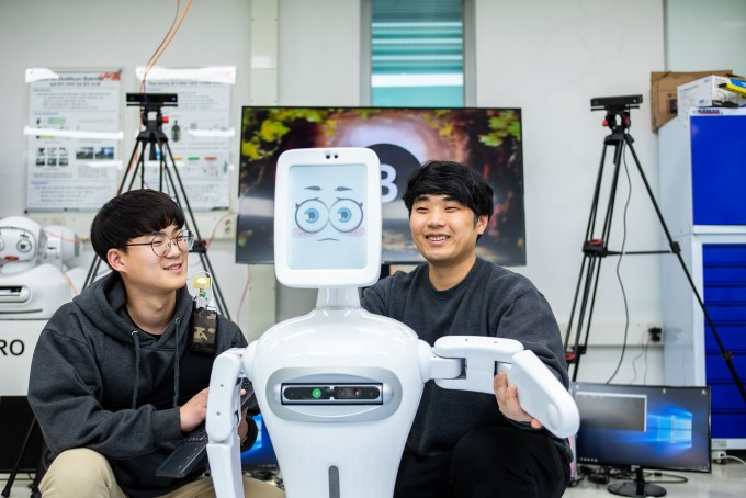 김문상 GIST 헬스케어로봇센터장 연구팀 연구자들이 자폐스펙트럼증후군 어린이를 위한 놀이 치료 로봇과 함께 자세를 취했다. 인공지능(AI)기술과 로보틱스가 결합한 로봇은 최근 다양한 질병을 보다 환자 친화적으로 치료할 대안으로 주목 받고 있다. 동아사이언스 제공