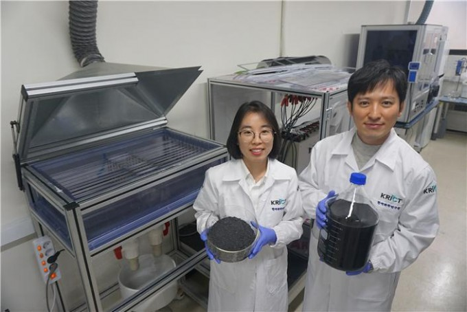 이제욱 한국화학연구원 책임연구원(오른쪽)과 권연주 연구원이 멀티 전극 시스템으로 생산한 그래핀 용액과 가루를 들고 포즈를 취했다. 두 연구원 뒤에 있는 장치가 차세대 전기화학 박리공정이 적용된 멀티 전극 시스템이다. 한국화학연구원 제공