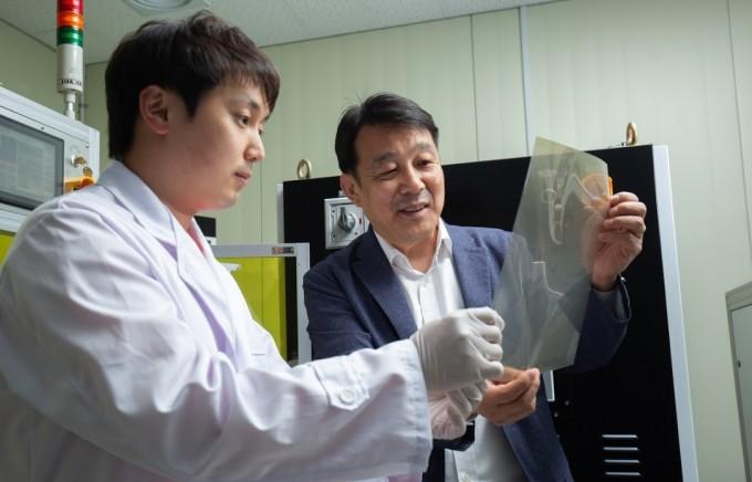 김대업 박사(右)와 윤지원 연구원(左)이 스마트 윈도우 필름 시제품을 확인하고 있다. 연구팀이 개발한 스마트 윈도우는 가시광선 투과도는 높이면서도 적외선 투과율은 한층 낮춰 기능을 개선했다. 동아사이언스DB