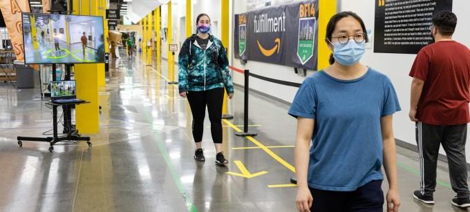 아마존은 직원들의 사회적 거리두기를 돕기 위한 ′거리두기 어시스턴트′를 개발했다고 밝혔다. 모니터 속 직원들의 발 아래에 증강현실(VR)로 구현된 원이 보인다. 아마존 제공