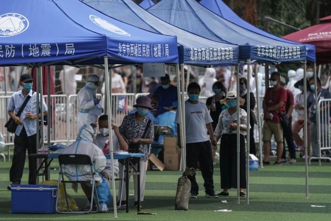 중국 베이징의 최대 농수산물 도매시장인 신파디 시장을 방문했거나 근처에 사는 주민들이 신종 코로나바이러스 감염증(코로나19) 검사를 받기 위해 15일 광안 스포츠 센터에 설치된 검사소에서 긴 줄을 이루고 있다. 최근 베이징에서는 신파디 시장을 중심으로 코로나19가 재확산하고 있다. 연합뉴스 제공