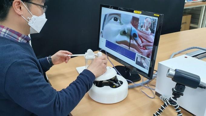 의료진은 ′마스터 장치′를 이용해 모니터로 환자의 상태를 확인하며 안전하게 검체를 채취할 수 있다. 한국기계연구원 제공