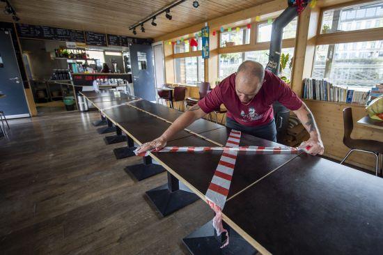 스위스 제네바의 한 식당에서 주인이 책상위에 ′사회적 거리두기′ 간격 유지를 위해 테이프를 붙이고 있다. EPA/연합뉴스