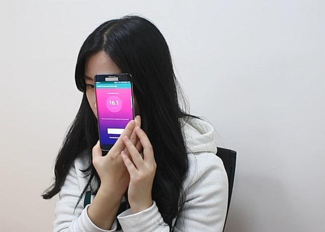 구민재 연세대 신소재공학과 연구원이 코르티솔을 측정하도록 개발된 스마트렌즈를 이용해 스트레스 수치를 측정하고 있다. 스마트렌즈를 착용한 후 스마트폰을 눈 주위로 가져가 태그하면 정확한 스트레스 호르몬 수치를 실시간으로 확인할 수 있다. 기초과학연구원(IBS) 제공