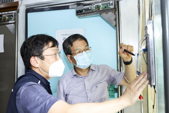 함상용 한국기계연구원 첨단생산장비연구부 로봇메카트로닉스연구실 책임기술원(오른쪽)이 자동 밸런스 도어 기술을 백진기 세이인 대표에게 설명하고 있다. 한국기계연구원 제공