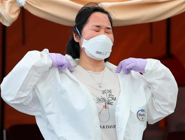 서울 양천구 보건소 선별진료소에서 한 의료진이 근무 교대를 위해 방호복을 벗고 있다. 연합뉴스 제공