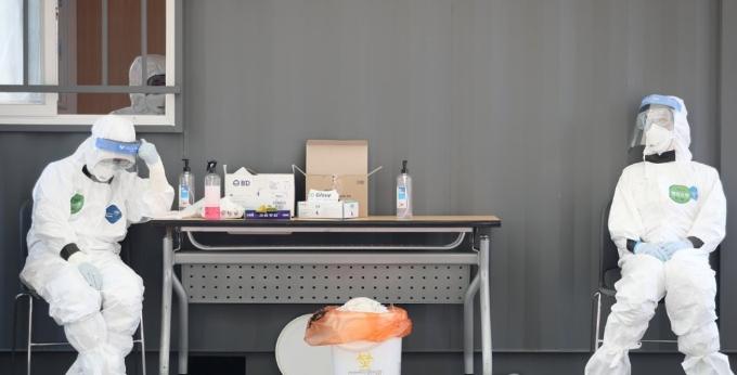오후 송파구 잠실야구장에 설치된 드라이브 스루 선별진료소에서 의료진이 의자에 앉아 잠시 쉬고 있다. 연합뉴스 제공