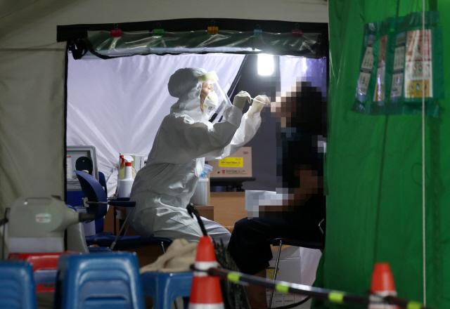 의료진이 26일 오후 광주 서구청에 마련된 코로나19 선별진료소에서 검체를 채취하고 있다.  연합뉴스 제공