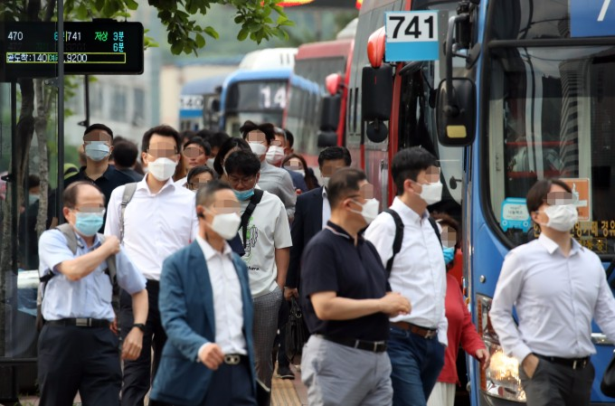 15일 서울 중구의 한 버스 정류장에서 마스크를 쓴 시민들이 출근을 서두르고 있다. 연합뉴스 제공