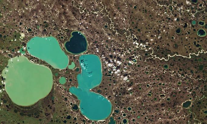 북극권의 영구동토층이 녹는 현상은 기후변화 학자들이 가장 우려하는 사태 중 하나다. 땅 속 얼음에 갇혀 있던 이산화탄소와 메탄이 방출돼 기후변화를 가속화할 수 있어서다. 최근 영구동토층 기온은 올라가고 있고 녹아 늪처럼 변한 지형이 자주 발견되고 있다. 사진은 시베리아 북서부 야말 지역에 형성된 영구동토층의 2018년 8월 모습을 촬영한 위성 영상이다. 유럽우주국 제공