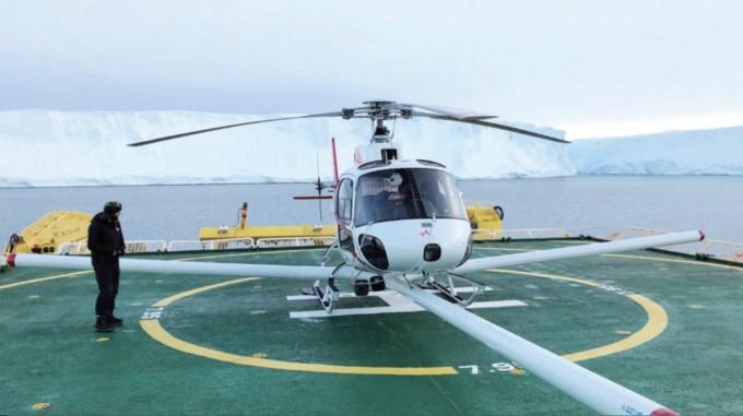 서남극 아문센해에 정박한 아라온호에서 스웨이츠 빙하로 이동하기 위해 준비 중인 헬리콥터. 뒤에 보이는 흰 절벽이 스웨이츠 빙하다. 아리랑 5호의 영상레이더를 활용하면 사전에 빙하 밑 지형을 확인할 수 있다. 극지연구소 극지기술개발지원부 제공