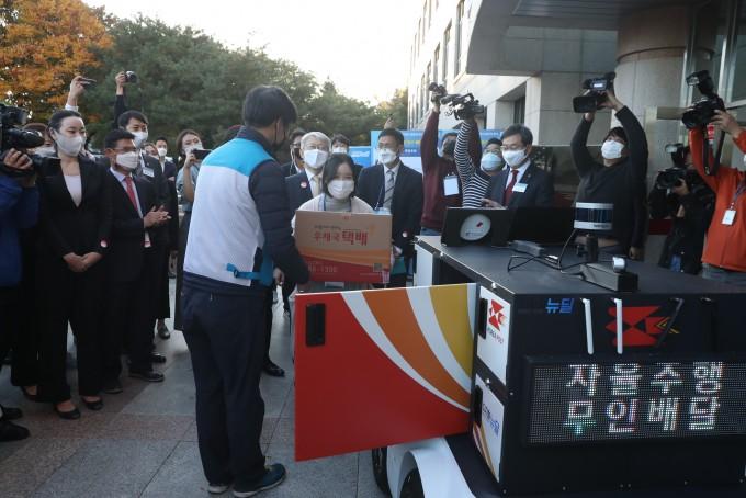 집배원이 추종로봇에서 짐을 꺼내 수취인에게 전달하고 있다. 과학기술정보통신부 제공