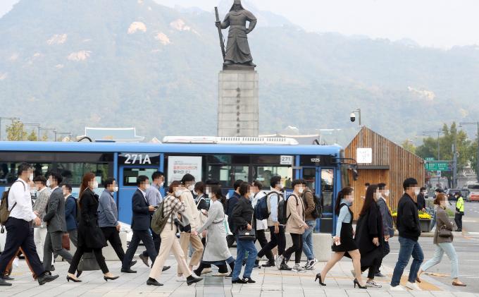 코로나19 사회적 거리 두기를 1단계로 완화한 12일 오전 시민들이 마스크를 쓰고 서울 광화문 사거리를 지나고 있다. 연합뉴스 제공
