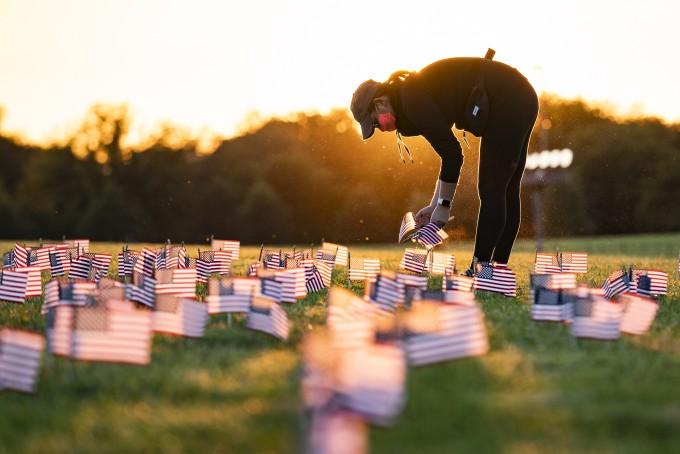미국의 코로나19 누적 사망자 수가 20만명을 넘어선 것으로 집계된 지난달 21일(현지시간) 코로나19 희생자 추모 프로젝트 자원봉사자들이 워싱턴 DC 내셔널몰 잔디밭에 성조기를 꽂고 있다. EPA/연합뉴스 제공