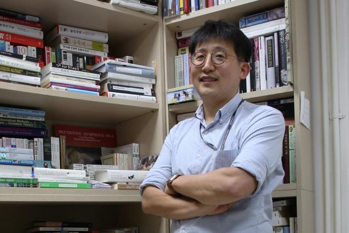 김찬수 한국과학기술연구원(KIST) 계산과학연구센터 연구원이 책이 가득한 연구실 서재에 기대 카메라를 응시하고 있다.