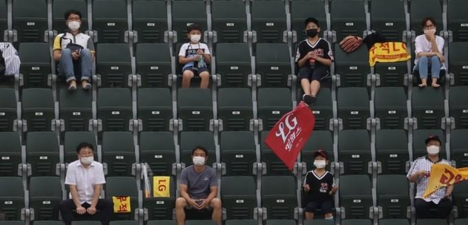 야구팬들이 지난달 31일 오후 서울 송파구 잠실야구장에서 좌석 간 거리두기를 유지하며 경기를 관람하고 있는 모습이다.  연합뉴스 제공